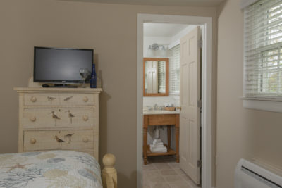 A television on the nightstand with bathroom in the background