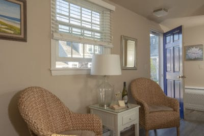 2 wicker chairs and nightstand with lamp and cheese and wine