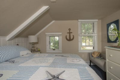 King room with nautical bedspread and decor overlooks teh gardens of the Ships Knees Inn