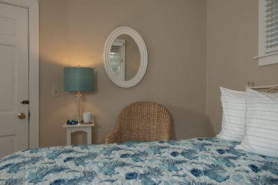 oval mirror and bedside lamp decorate the wall of the queen room #10