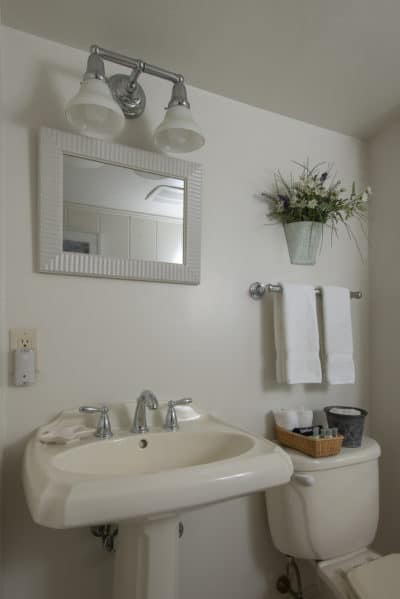 En-suite bathroom with sink and mirror with adequate lighting