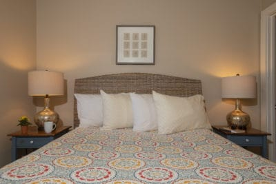 A queen bed with several plush pillows