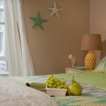 Deluxe room 9 with fruit on bed and coastal starfish wall decor