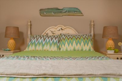 Room 9 quuen bed straight on with coastal art above