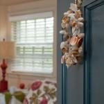 Deluxe King Room 16 with door ajar and shell wreathe