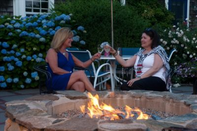 Guests toast a glass of wine at the firepit on our patio