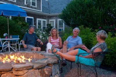 Guests lounge in the evening at our firepit and enjoy a glass of wine