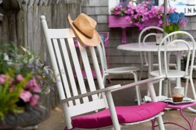 a rocking chair with pink cushion andsunhat