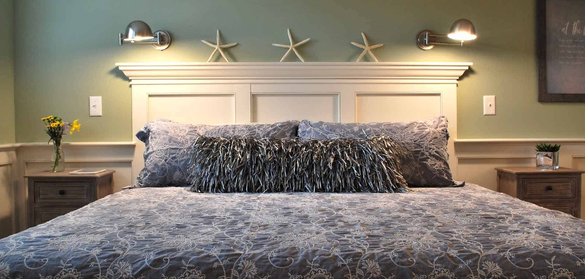 A chic gray bedspread and pillows with starfish decor above the headboard