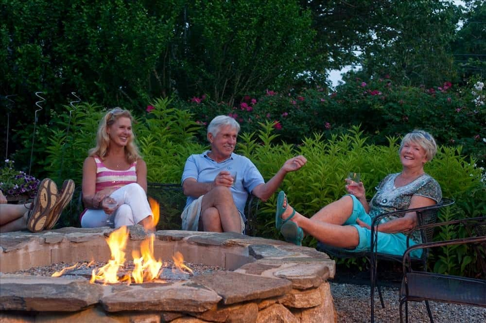 2 couples enjoying conversation by the fire pit
