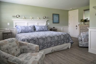 The deluxe king room bed with tasteful linens and decor