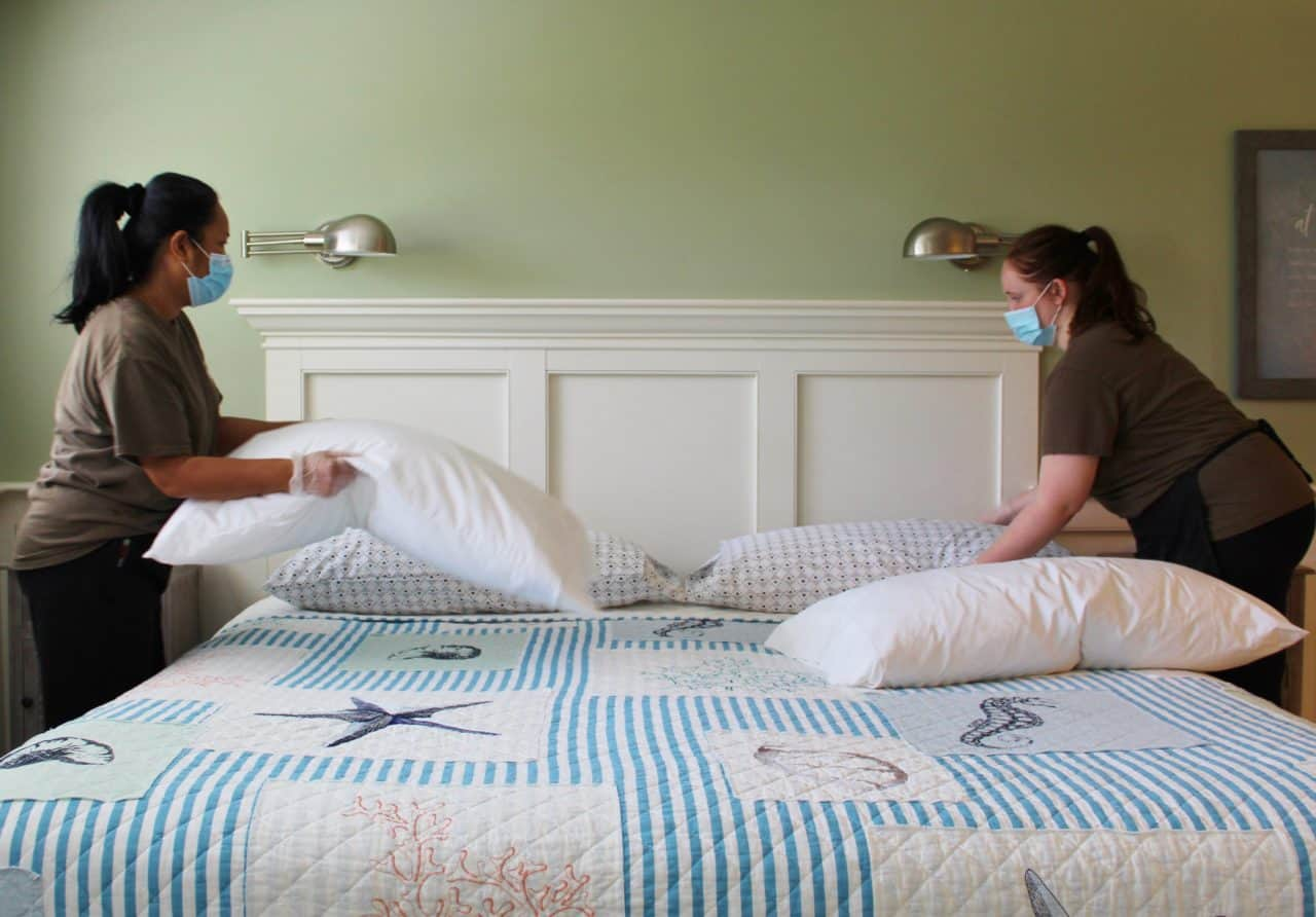 Masked housekeepers prepare the beds in the Ships Knees Inn