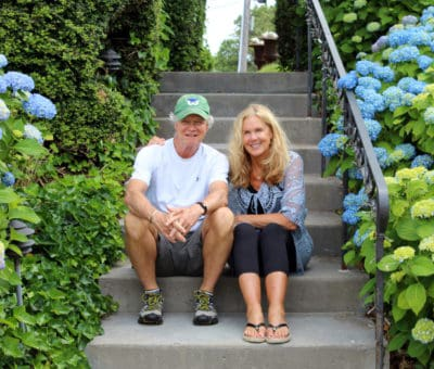 Peter and Denise Butcher sit on steps surrounded by hydrangea flowers
