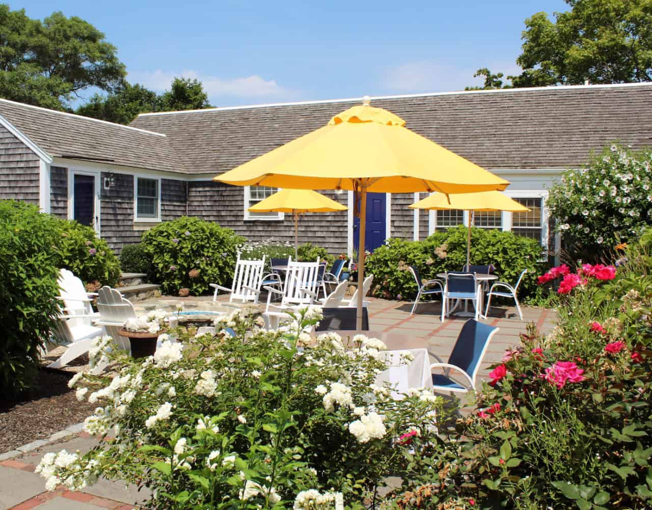 Colorful patio area with flowers and yellow umbrellas