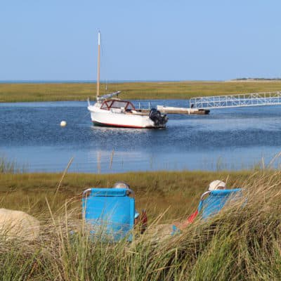 A couple sit by the wtaer in Nauset Marsh