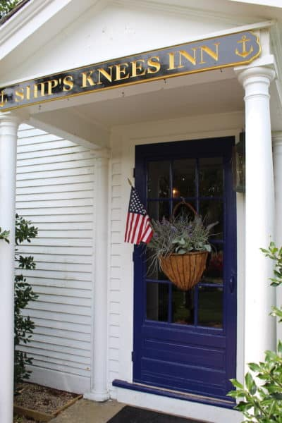 The office door at the Ships Knees Inn with sign and USA flag
