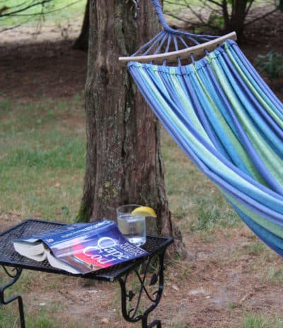 A hammock with a book and glass of water with lemo
